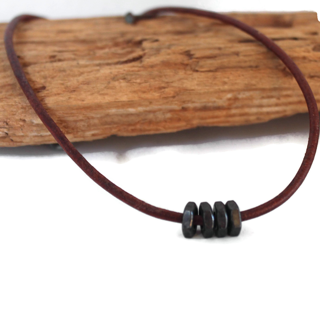 black-hex-nut-brown-leather-men's-necklace-on-wood-on-white-background